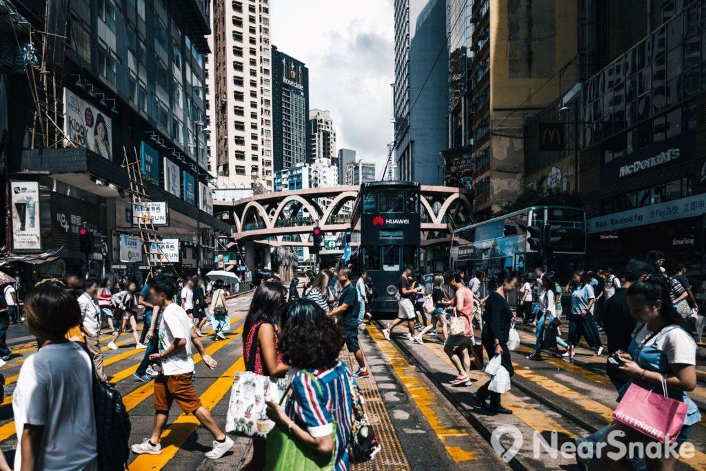 怡和街圓形天橋位處銅鑼灣鬧市中心,地面人流如鯽,橋上不動如山,動靜相襯,相映成趣。
