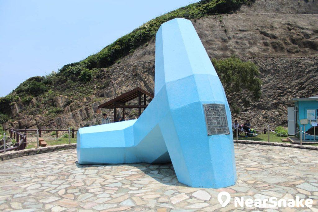 萬宜水庫紀念碑座落東壩上,巨形藍色錨形石的造型相當顯眼。