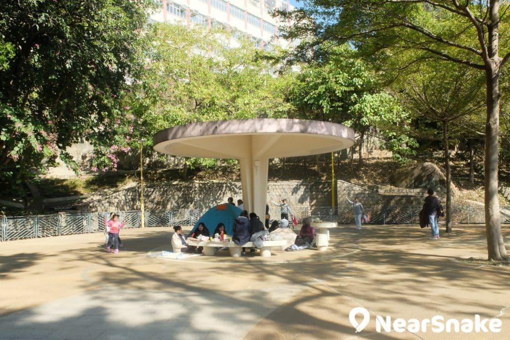 界限街花墟公園遠角的涼亭,前面有一片空地,每到周末總見家長坐著聊天,小朋友在空地上追逐。