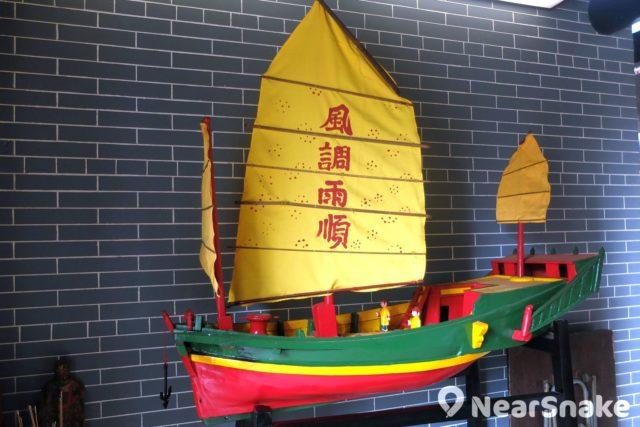 譚公廟內小龍舟旁擺放著一艘小帆船,帆上寫有「風調雨順」四字。