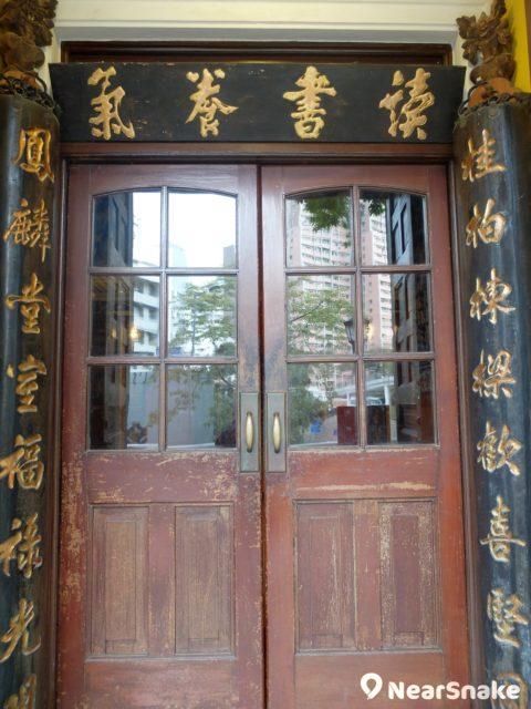來到香港大學美術博物館大門,左右擺放著刻有對聯的木柱,柱上還有雕飾,配以橫扁及古撲大門,一片書卷氣息。