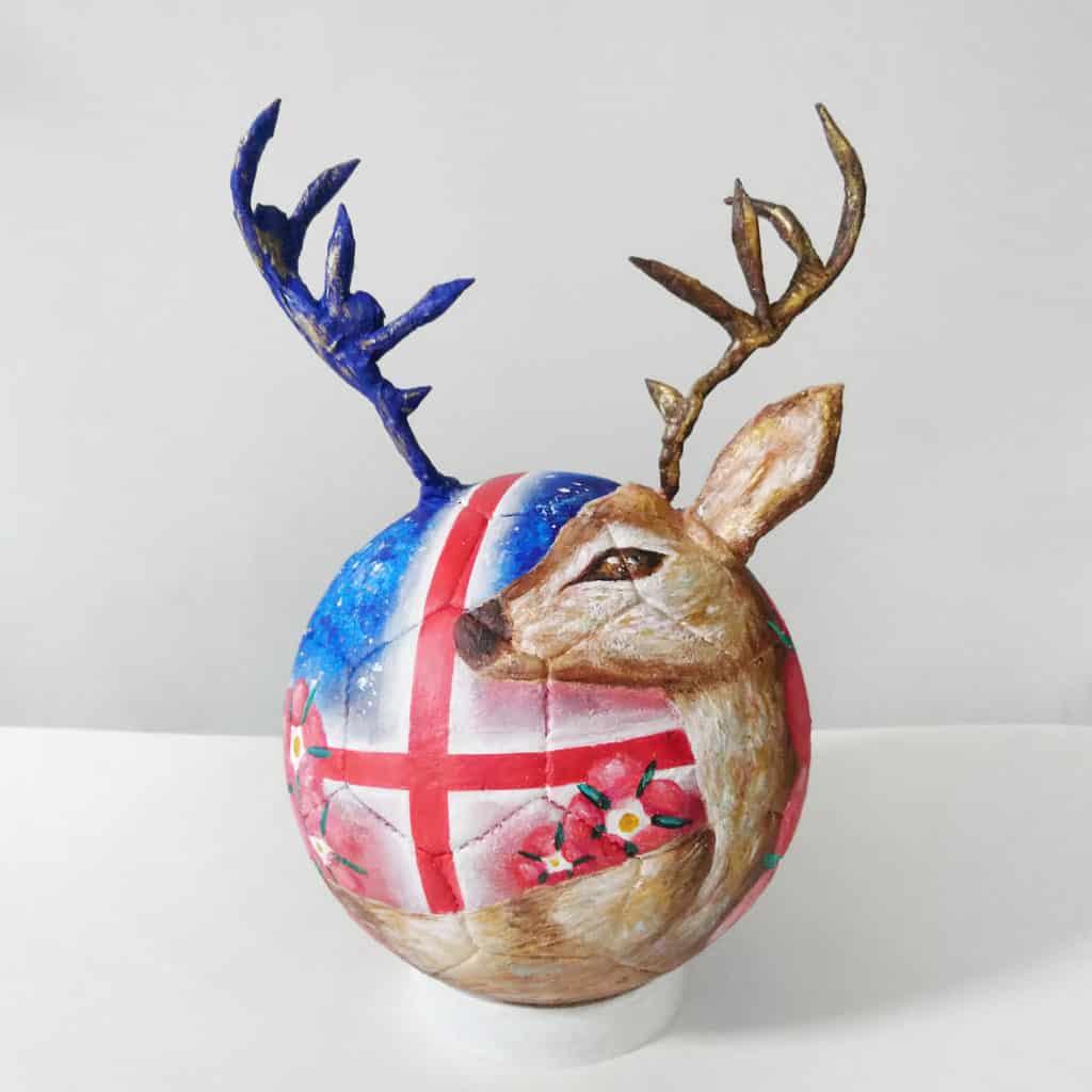 香港知專設計學院學生足球作品「英格蘭X鹿 」:足球根據英格蘭十字旗、英格蘭球隊,以及本年度世界盃標誌的概念而繪畫。配上鹿及球隊標誌中代表英格蘭的都鐸玫瑰,以球隊球衣的藍、紅、白為顏色主調。