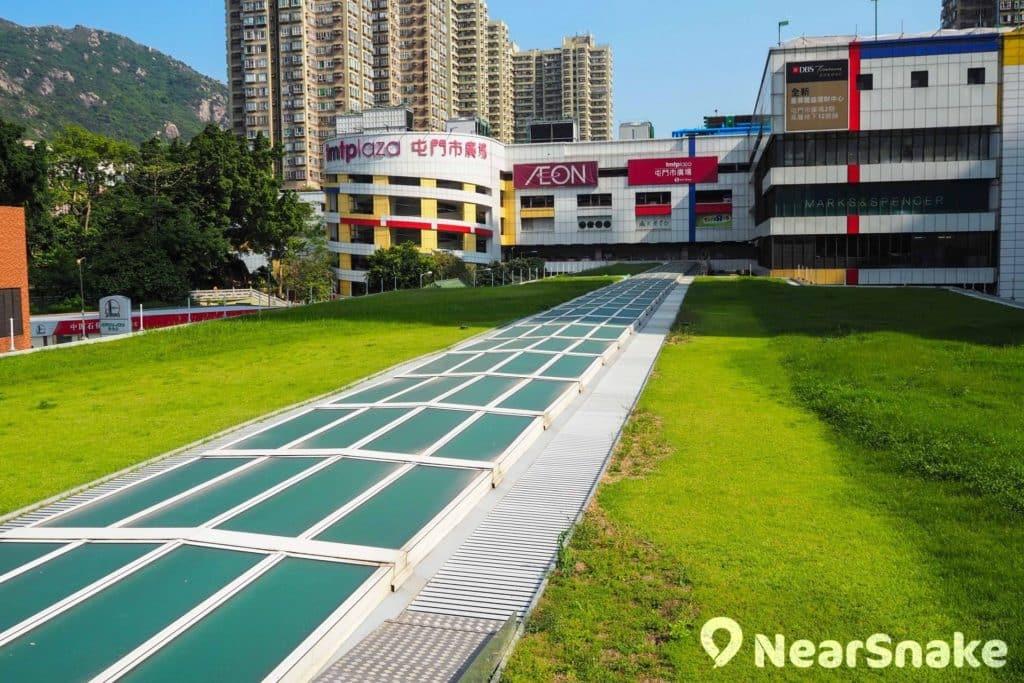 從杯渡輕鐵站可遠眺屯門市廣場一期,可看到中間的高速公路加建蓋頂,再鋪上草皮,營造綠化氣息。