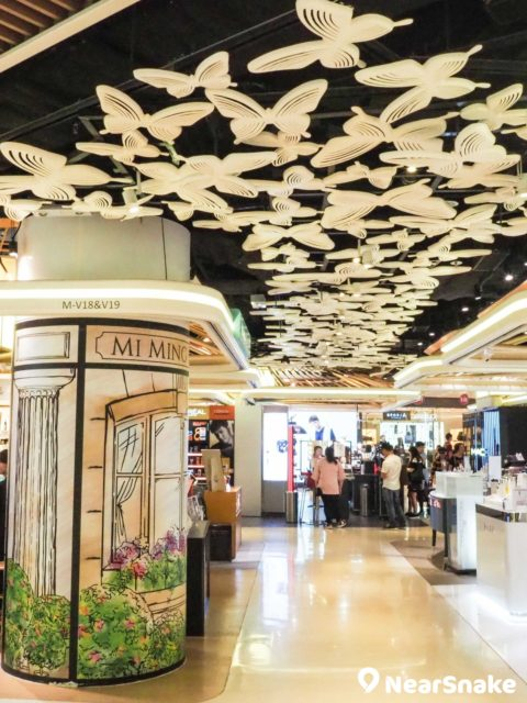 V City 商場化妝品專區的天花部分,由 500 隻立體蝴蝶裝置組成,展現出蝶群飛舞的美態,乃出自室內設計師蔡明治的手筆。