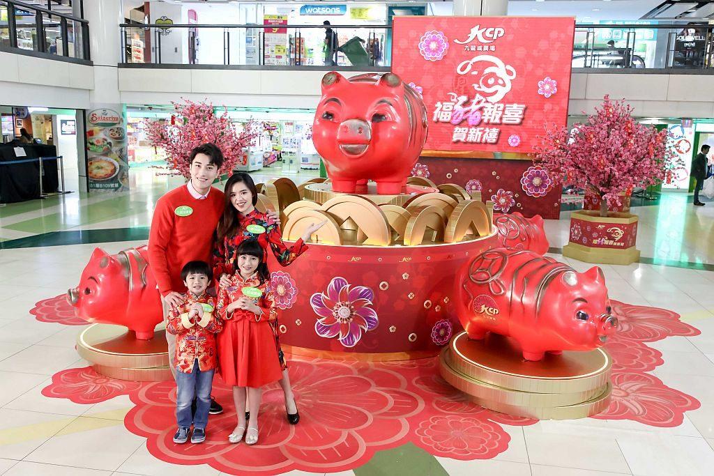 九龍城廣場中庭擺放逾 1 米高巨型傳統塑膠豬仔錢,身旁還有四小豬「紅」霸四方。