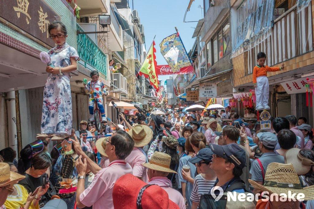 長洲飄色巡遊由身高不高於 42 吋和體重少於 35 磅的小孩被支架撐著,扮演著歷史人物、虛構人物、新聞或政治人物進行巡遊。