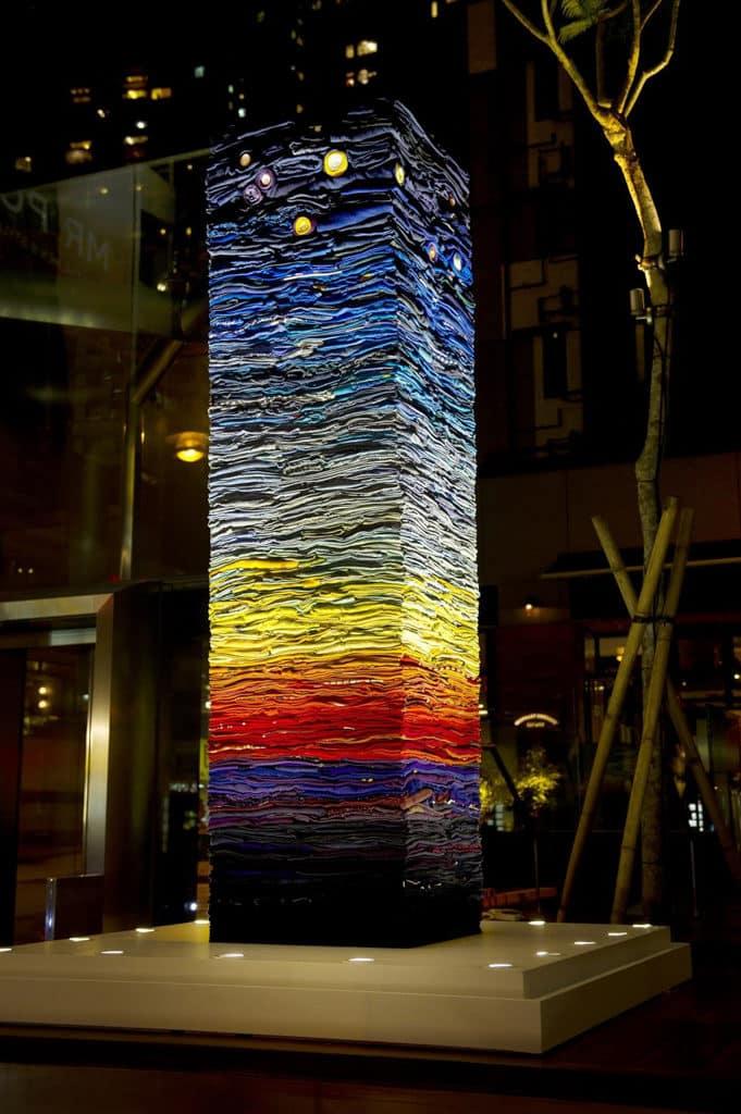 """星街小區:""""You Are My Other Me"""" 大型環保藝術裝置 高聳的柱子以一件件經過精心摺叠的二手服裝巧妙地堆叠而成。"""